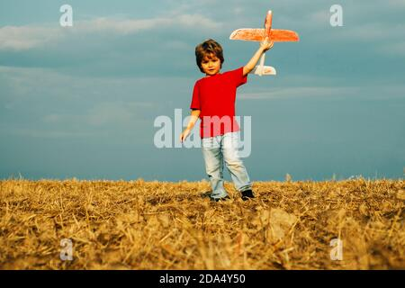 Little cute boy playing with a toy airplane. The concept of child kindness and childhood. Children run with plane on field. Child playing with model