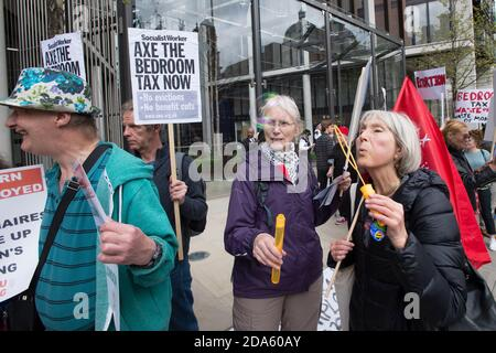 Protest to mark the first anniversary of the 'Bedroom Tax', outside One Hyde Park, one of London's most expensive residence. The Welfare Reform Act 2012, which came into force on 1 April 2013 included changes housing benefit rules. These changes include an 'under-occupancy penalty' which reduces the amount of benefit paid to claimants if they are deemed to have too much living space in the property they are claiming housing benefit on, these changed became know as the 'Bedroom Tax'.  One Hyde Park, Knightsbridge, London, UK.  5 Apr 2014 - Stock Photo