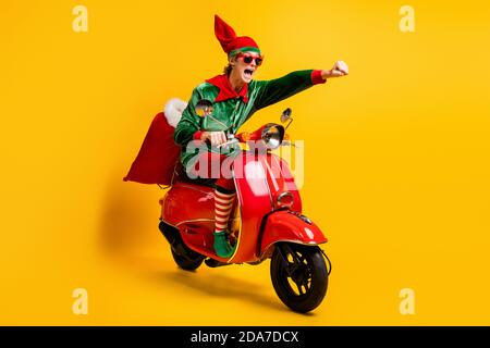 Portrait of his he nice attractive cheerful energetic funny guy elf riding moped bringing fast express speed sack gifts December sale isolated over - Stock Photo