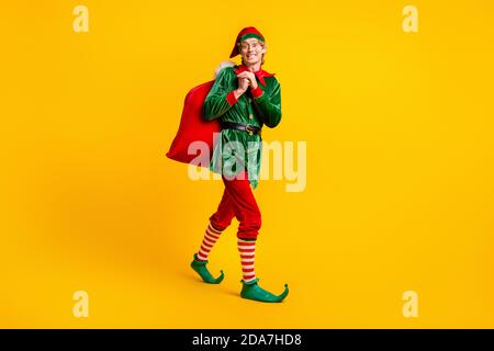 Full length body size view of his he nice attractive cheerful funny guy elf going carrying bringing sack gifts delivery Eve Noel isolated over bright - Stock Photo