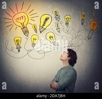 Creative businessman, thinking of great ideas, looking at bright lightbulbs on the wall. Business worker search for solutions to solve the problems, g