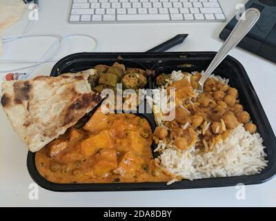 Eating indian food in container during working. Chickpeas, rice, naan in plastic container on a computer desk - Stock Photo
