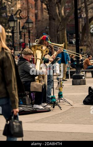 Street musicians busking with tuba and trombone in Washington Square Park, Greenwich Village, NYC, New York - Stock Photo