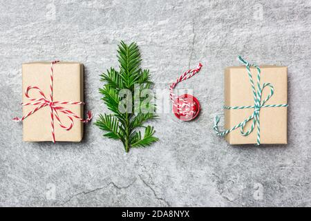 Christmas composition. Gifts, evergreen tree and red Christmas ornament on gray stone background. Christmas, winter, new year concept. Flat lay, top v