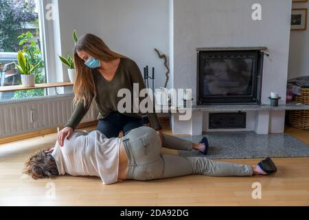 First aid measures under corona conditions, stable lateral position, after an accident in the home, with a mouth and nose mask, when first aid is give