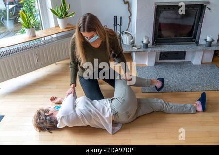 Erste Hilfe Massnahmen unter Corona-Bedingungen, Stabile Seitenlage,  nach einem Unfall im der Wohnung, mit Mund-Nase-Maske, beim ErsteHilfe Leistende