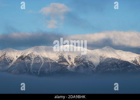 The sun rises on the snow-capped east slope of the Lemhi Range shrouded in clouds on a winter morning.