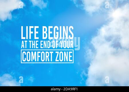 Life begins at the end of your comfort zone inspirational quote against blue sky with clouds background. Making a change, evolving or personal improve