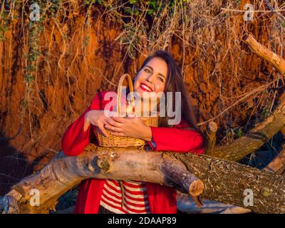 Sunset stunning young woman with wicker basket standing inclined on fallen dried tree trunk direct looking at camera away happy smiling Red lips mouth - Stock Photo