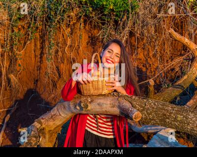 Sunset stunning young woman standing holding wicker basket inclined on fallen dried tree trunk direct looking at camera happy smiling Red lips mouth - Stock Photo