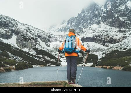 Active people in nature concept. Dressed bright orange jacket female backpacker enjoying the Velicke pleso (mountain lake) view as she have mountain w