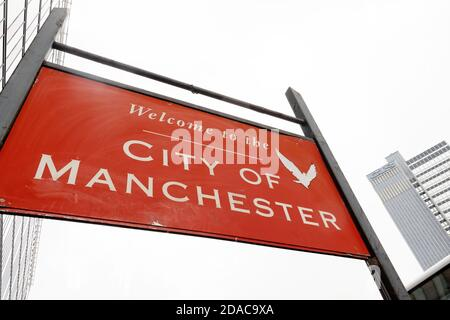 Road sign proclaiming: Welcome to the CITY OF MANCHESTER. The 118m tall CIS Tower building lies in the distance. - Stock Photo