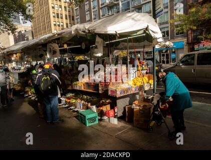Customers at a fruit stand in Chelsea in New York on Saturday, October 31, 2020.  (© Richard B. Levine) - Stock Photo