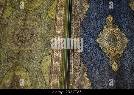 Closeup of colourful green and blue handmade Turkish carpets with intricate patterns and designs, Istanbul, Turkey - Stock Photo