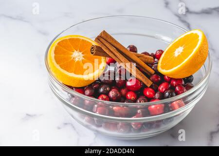 Fresh cranberries, cinnamon and oranges close up in a glass bowl on marble background. Ingredients for cooking cranberry sauce - Stock Photo