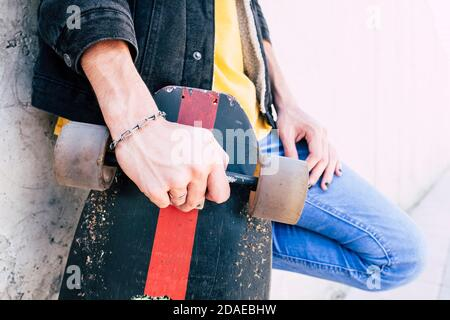 Close up of young man hands holding used trendy skateboard - concept of young people and urban lifestyle - alternative life for teen man - unrecognizable caucasian people in urban concept life