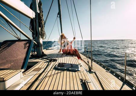 Beautiful young woman enjoy summer holiday vacation or excursion on sailboat with sun and ocean around - people enjoying life and lifestyle - travel and transport on sea concept