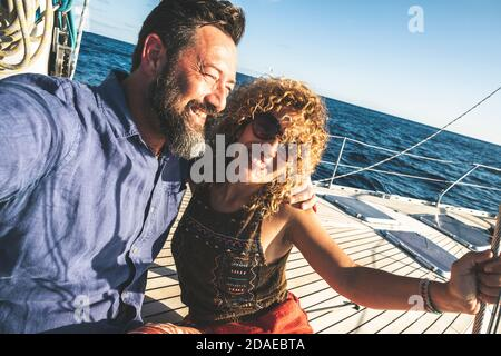 Happy adult caucasian couple together on a sailboat enjoy vacation or excursion - people in outdoor leisure activity on boat with blue ocean and sky around . happiness and love man and woman