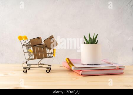 Toy shopping cart with boxes on the wooden desk with beautiful cacti and plant in design concrete pots. Gray walls. Shopping concept.