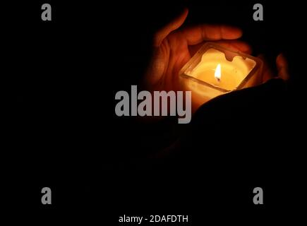 Hands holding a beautiful square shaped candle with glowing flame during festival celebrations of diwali or kalipuja in india. photo taken with dark b - Stock Photo