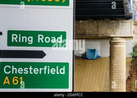 A pop-up tent pitched on Park Square roundabout, Sheffield under a Supertram bridge used by a homeless person sleeping rough - Stock Photo