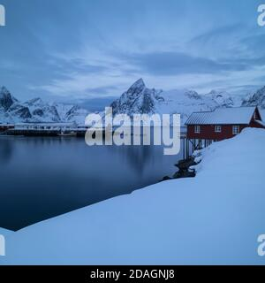 Olstind mountain peak and red rorbu cabins rising over snow covered coastline, Moskenesøy, Lofoten Islands, Norway - Stock Photo