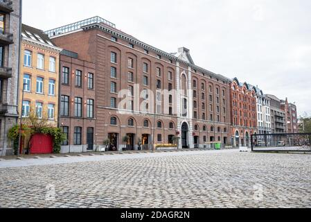 Row of brick warehouses converted in residential buildings in a port area on a cloudy winter day - Stock Photo