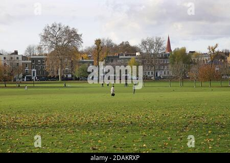 Walkers cyclists and dog-walkers enjoy a sunny autumn day on Peckham Rye Common, south east London, UK. - Stock Photo