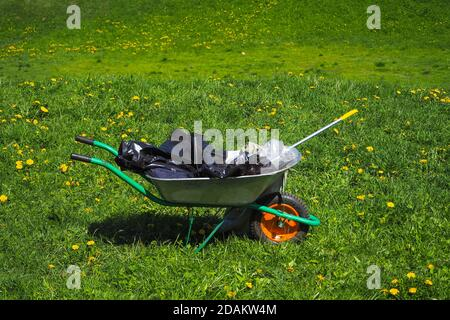 Cart with garbage on the green grass. Cleaning the Park after a barbecue in nature. - Stock Photo