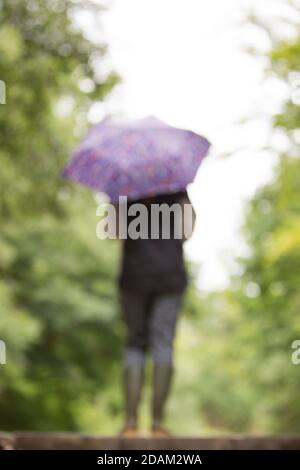 Rear view of blurred, out of focus woman in wellies isolated outdoors with umbrella. - Stock Photo