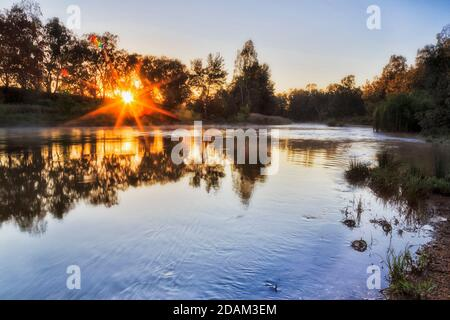 The rising sun over horizon in trees near Macquarie river in Dubbo town of Australia.