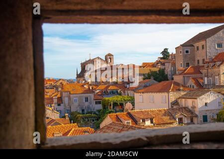 Roofs of many beautiful old houses and churches seen in the city of Dubrovnik, framed in a small window in a tower on the old city walls