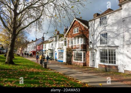 People strolling along the wide pavement of Tenterden High Street on a sunny autumn day, Kent, UK - Stock Photo
