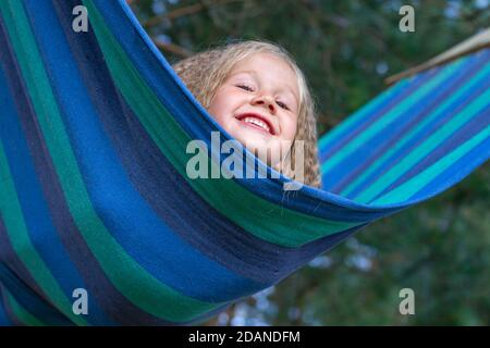 Little happy Caucasian girl with blond curly hair sways on multi-colored striped hammock. Portrait of a child, close-up. Peekaboo. Lifestyle. Carefree