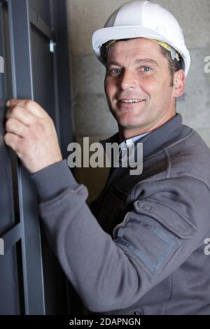 handsome young man installing bay window - Stock Photo