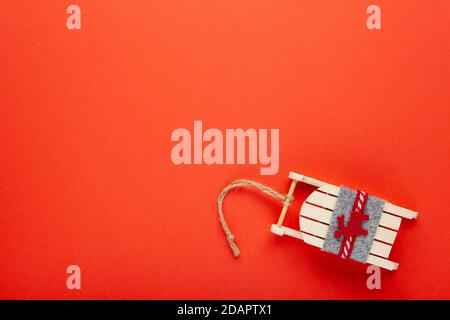 Christmas decoration, tree toy, wooden sled with deer on red background with copy space. Festive, New Year concept. Horizontal, flat lay. Minimal styl - Stock Photo