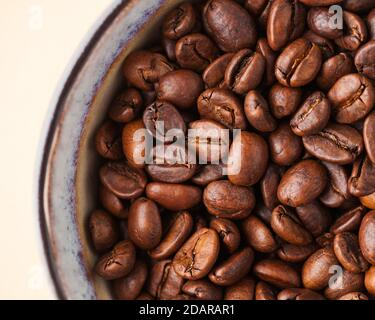 Coffee beans close-up on a light brown background. For screensavers, roasters and coffee sellers.