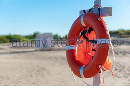 Bright lifebuoy and life jacket on the beach - Stock Photo