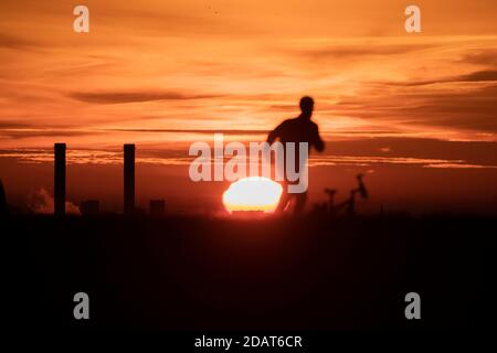 Berlin, Germany. 15th Nov, 2020. One person runs at sunrise on the Dragon Mountain. Credit: Christoph Soeder/dpa/Alamy Live News