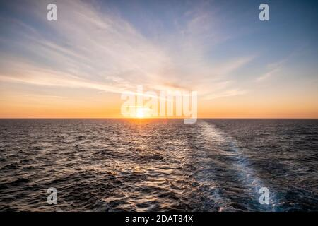 Sunrise over a calm Mediterranean Sea, seen from the stern of a cruise ship. - Stock Photo