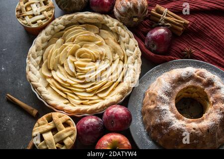 Dessert tarts on a table. Top view photo of various apple pies, cakes and tarts, fresh plums, apples and pumpkins. Autumn menu ideas.