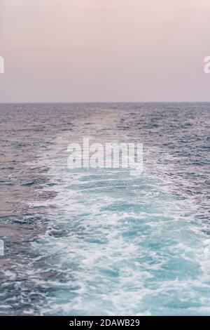 Water surface background. Blue sea water splashes with sun reflections. Ripples of water in the.