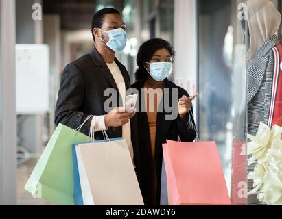 Happy young african american couple of shoppers in protective mask walk in mall, hold colorful bags