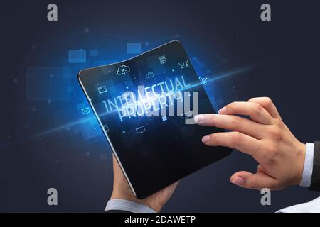 Businessman holding a foldable smartphone with INTELLECTUAL PROPERTY inscription, cyber security concept