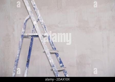 Single blue dirty aluminum folding metal step ladder leaning against grey plaster wall background - Stock Photo