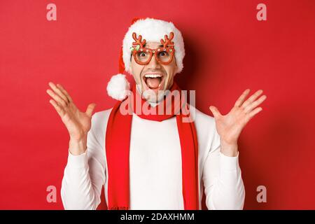 Concept of christmas, winter holidays and celebration. Image of surprised and happy man looking amazed, wearing party glasses and enjoying new year