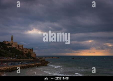 Tel-Aviv beach with a view of old Jaffa port in sunset light before rain storm. Israel. Sun rays glowing through clouds. Selective focus on sea waves.
