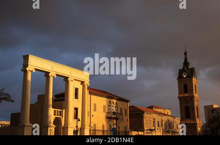 TEL AVIV-JAFFA, ISRAEL - MARCH 7, 2019: The Clock Tower built in Ottoman period and Ionian Columns decoration in Old Jaffa in sunset golden light rays