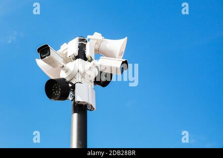 CCTV cameras, lights and loudspeakers are mounted on one pole under blue sky - Stock Photo