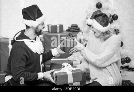 Opening christmas present. Couple in love happy enjoy christmas holiday celebration. Loving couple cuddle smiling while unpacking gift christmas tree background. Family prepared christmas gifts. - Stock Photo